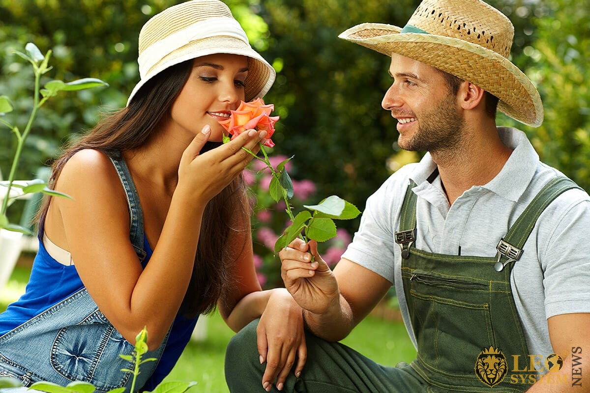 A man gives a beautiful flower to a woman in love