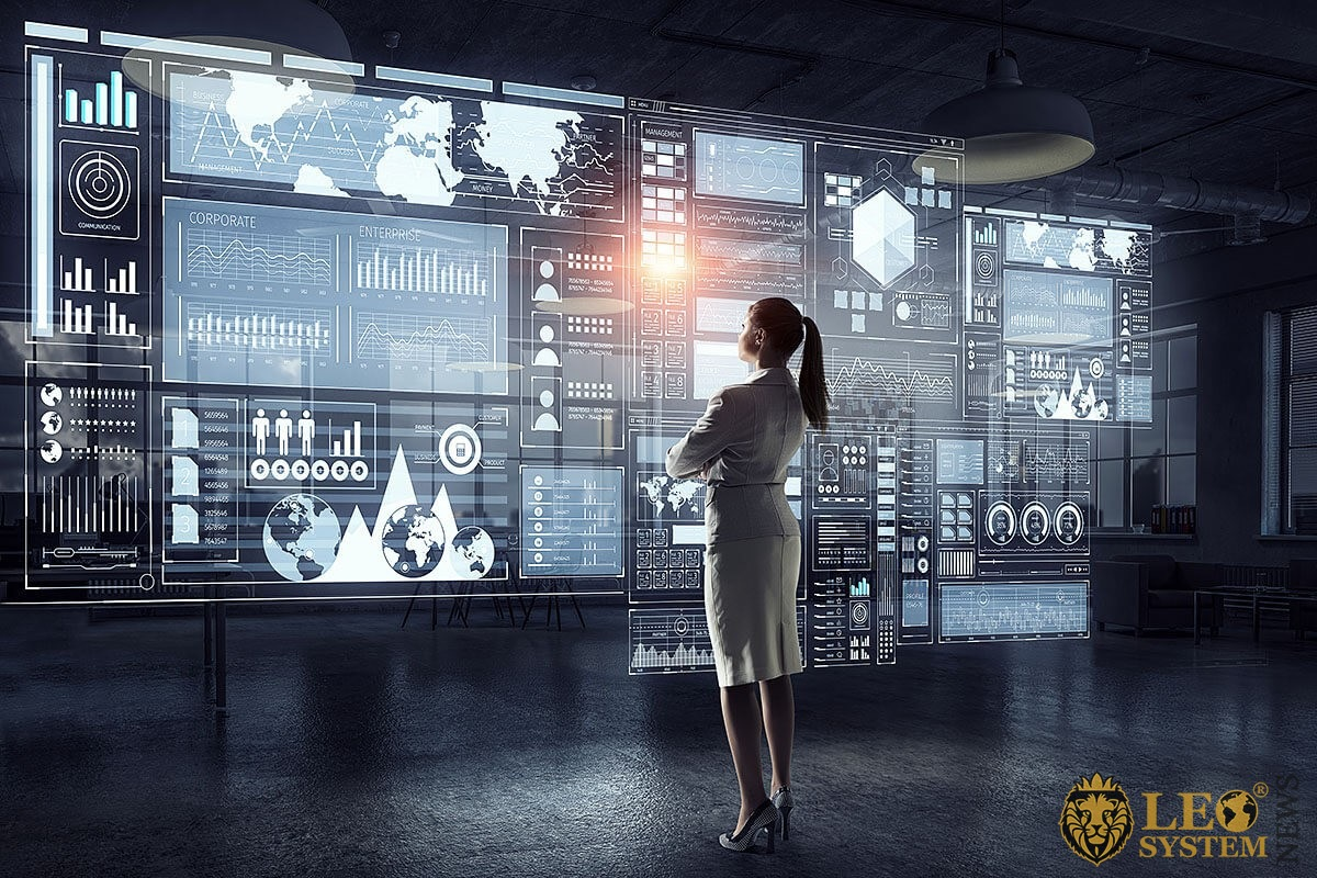 A woman looks at a large screen with graphs of economic development
