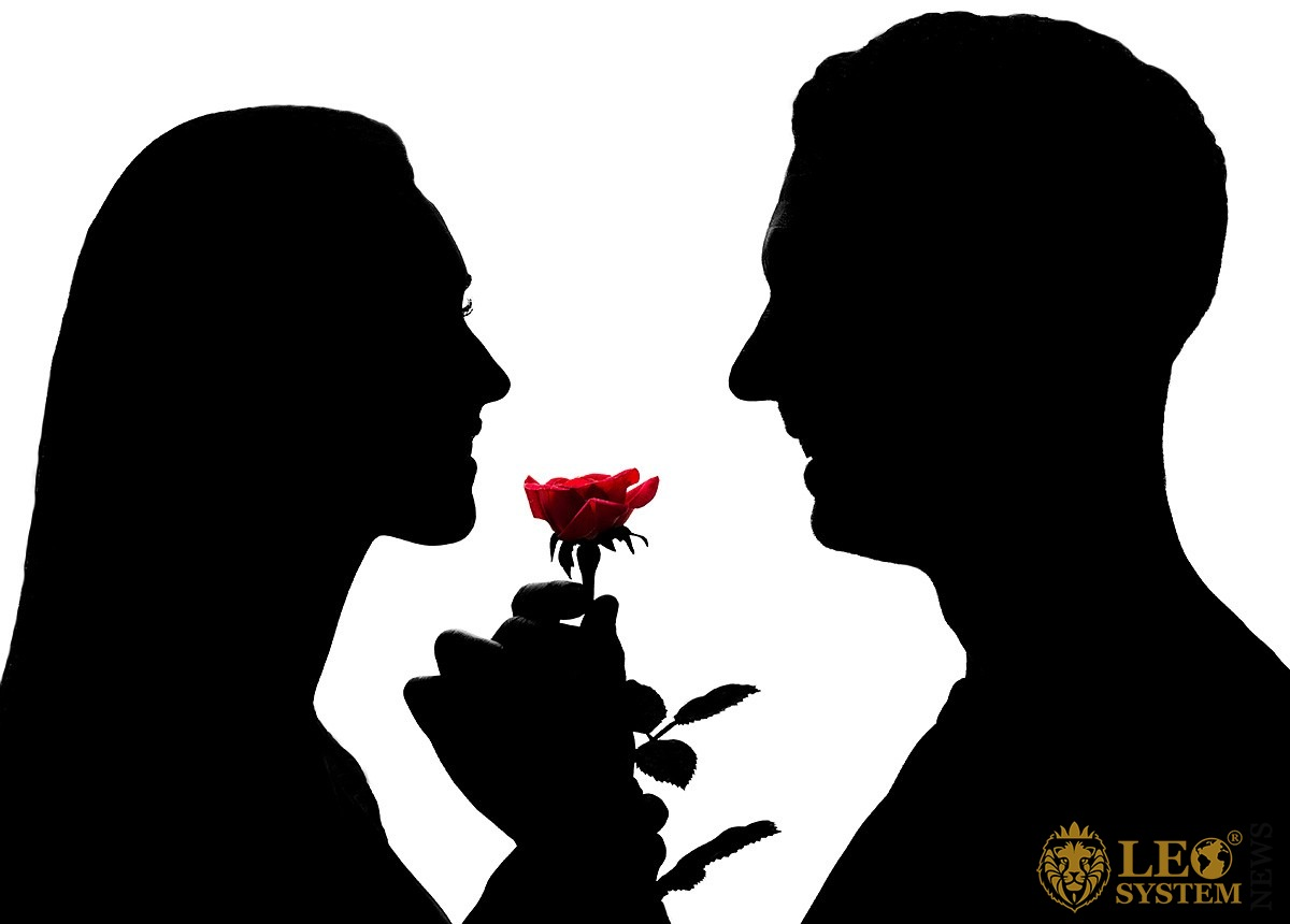 Image of a man in love who gives a red flower to his woman