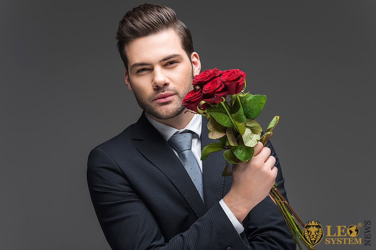 Loving handsome man in a suit and with flowers