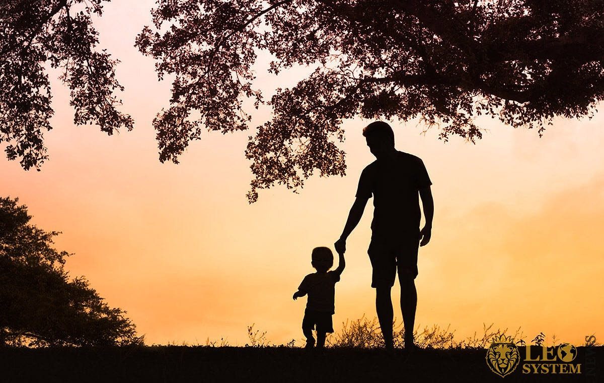 Father walks with his son at sunset