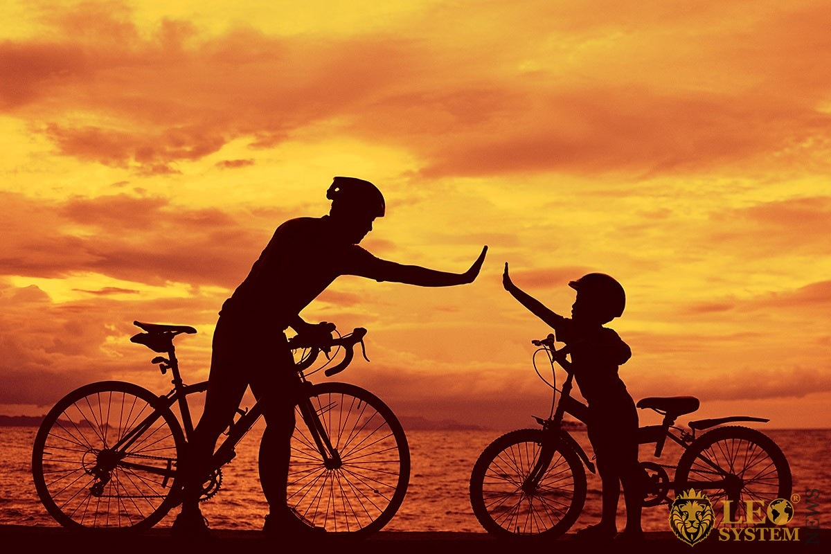 Father and son ride bikes by the sea