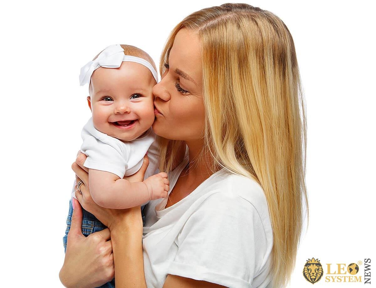 Loving mother kisses her baby tenderly