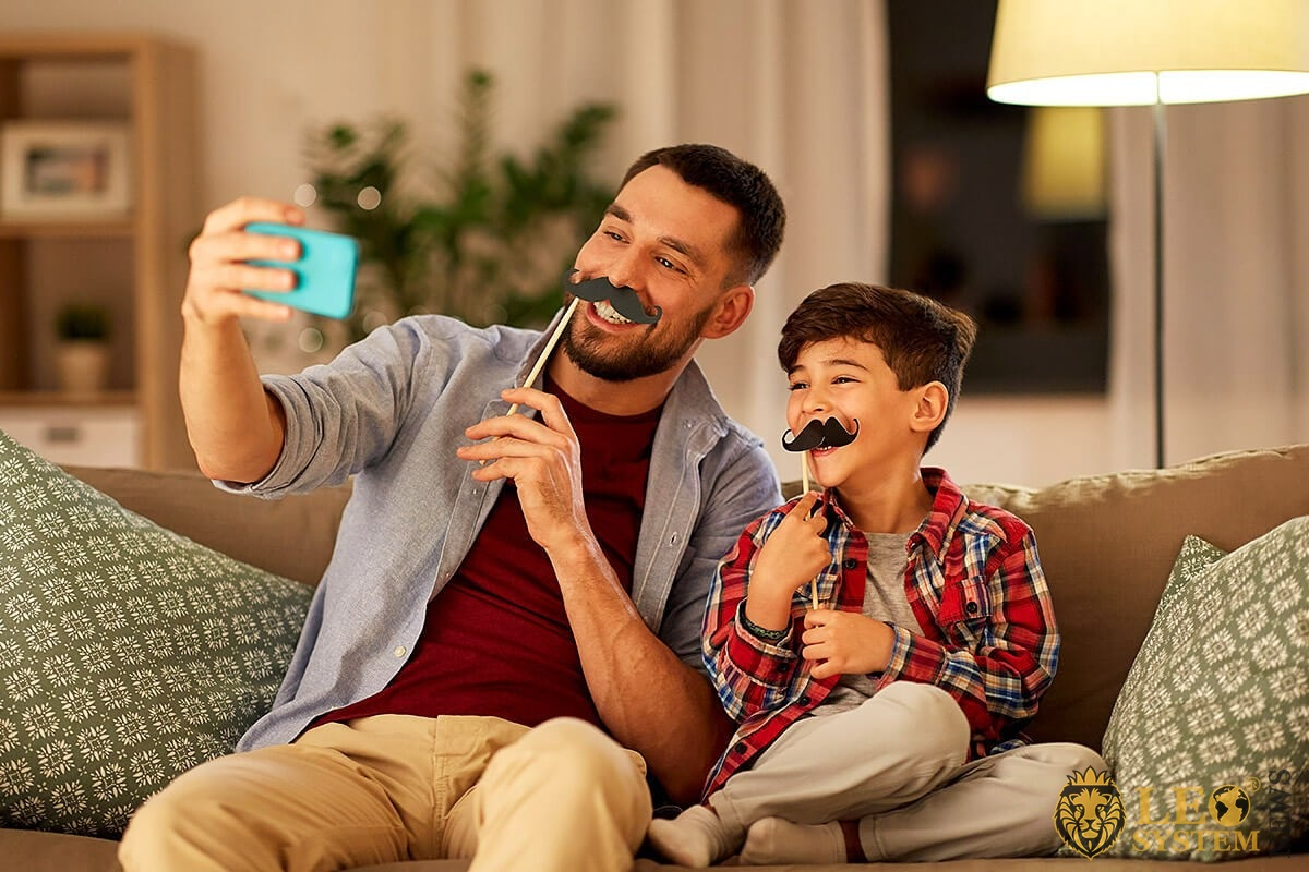 Father and son play a game on a mobile phone