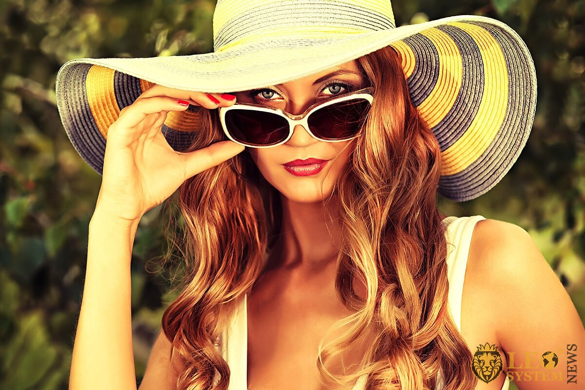 Beautiful woman in a big hat and sunglasses