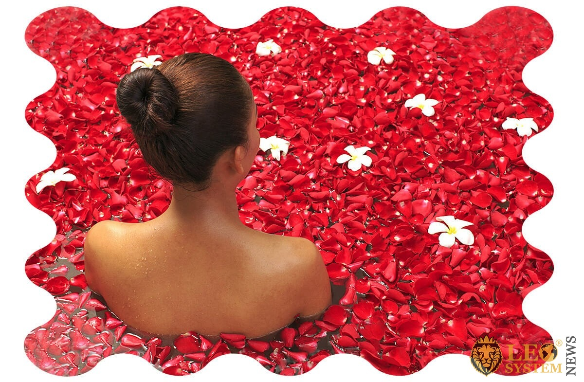 Woman relaxes her body in a bath with rose petals
