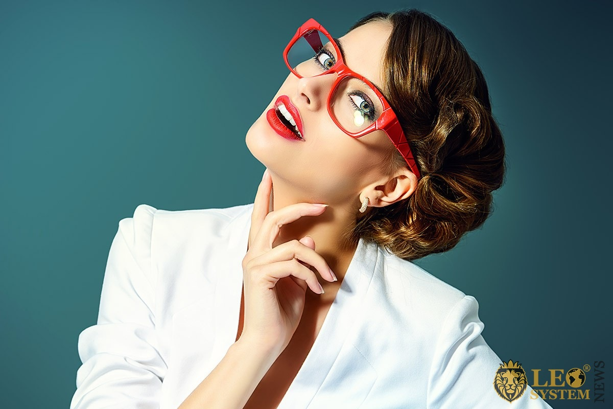 Pretty woman in a white suit and red glasses