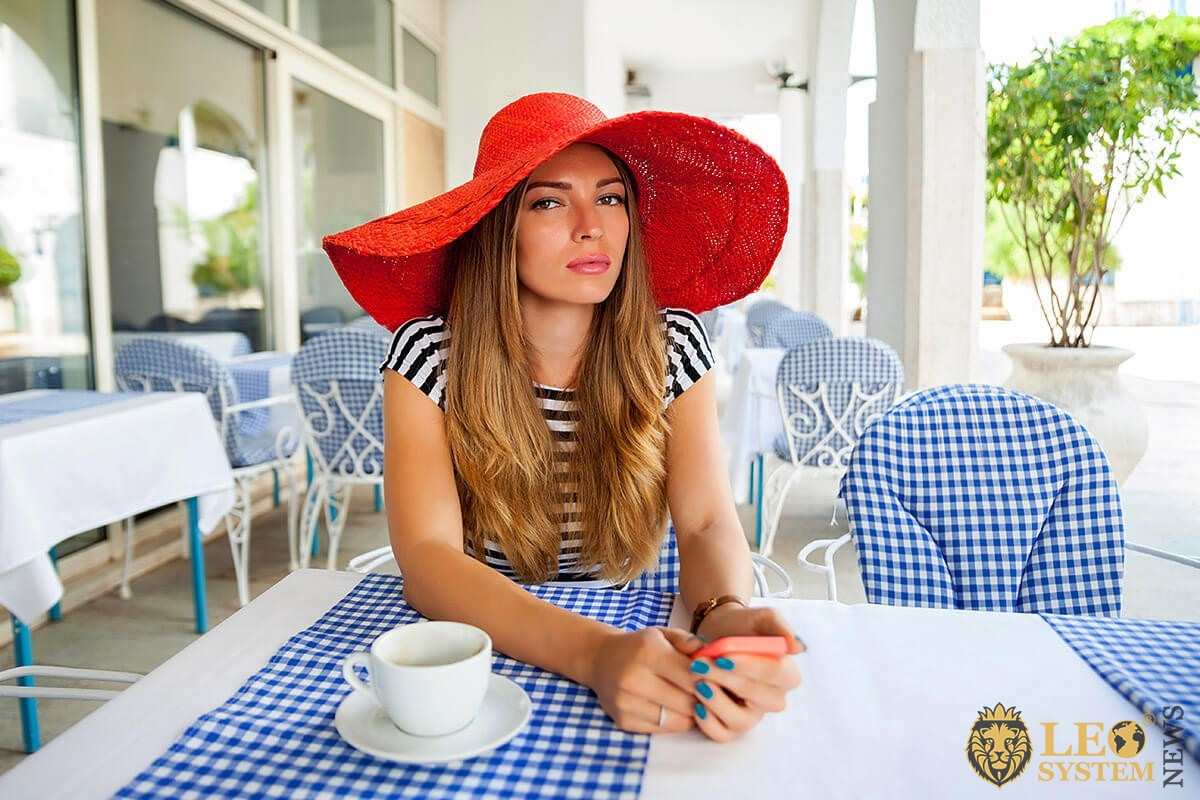 Pretty woman in a hat waiting for a man in a cafe
