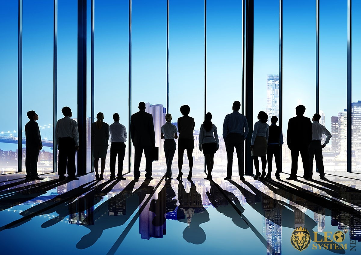 Image of a group of business people looking out the window at tall buildings