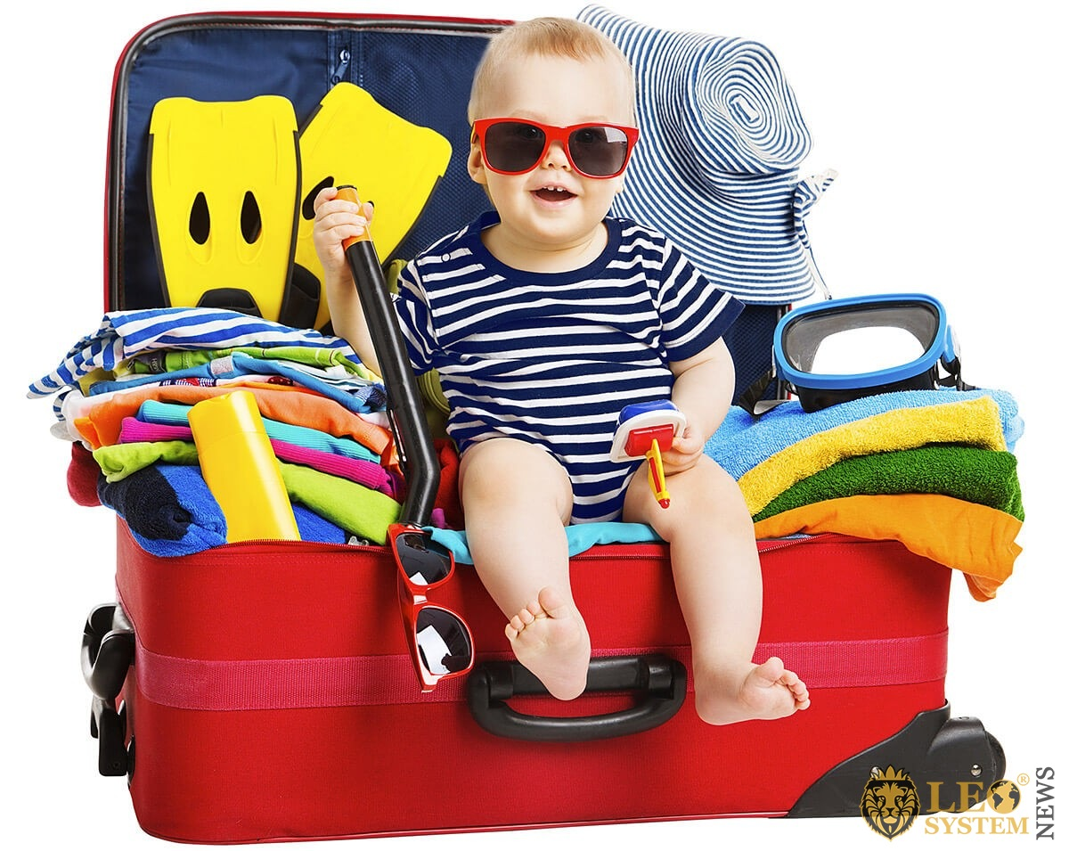 Cheerful child packed his own suitcase for a trip