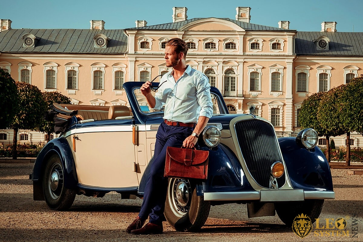 Image of vintage car and a man with a briefcase