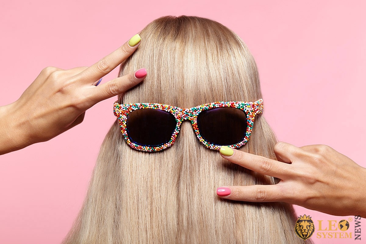 Image of beautifully dyed female hair and sunglasses