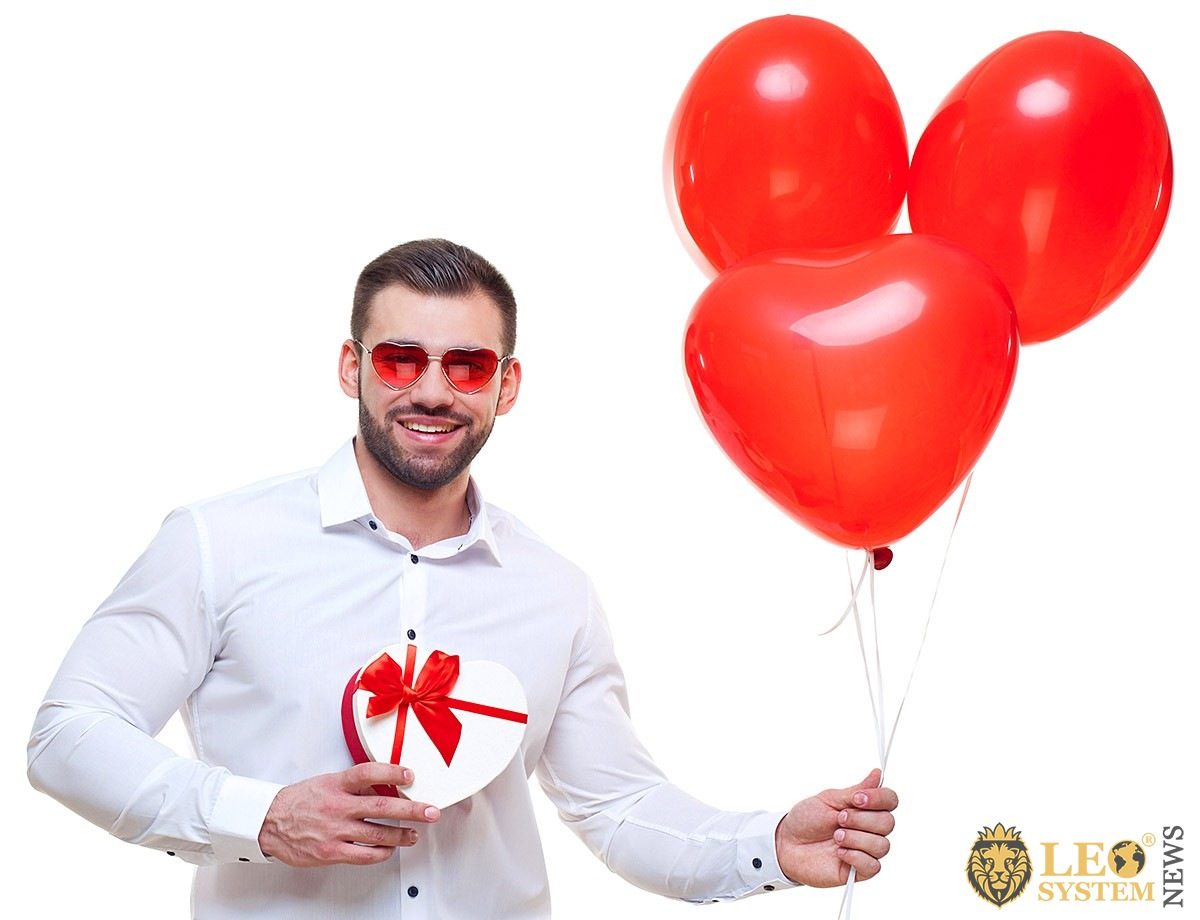 Young man with a box of chocolates and red balloons
