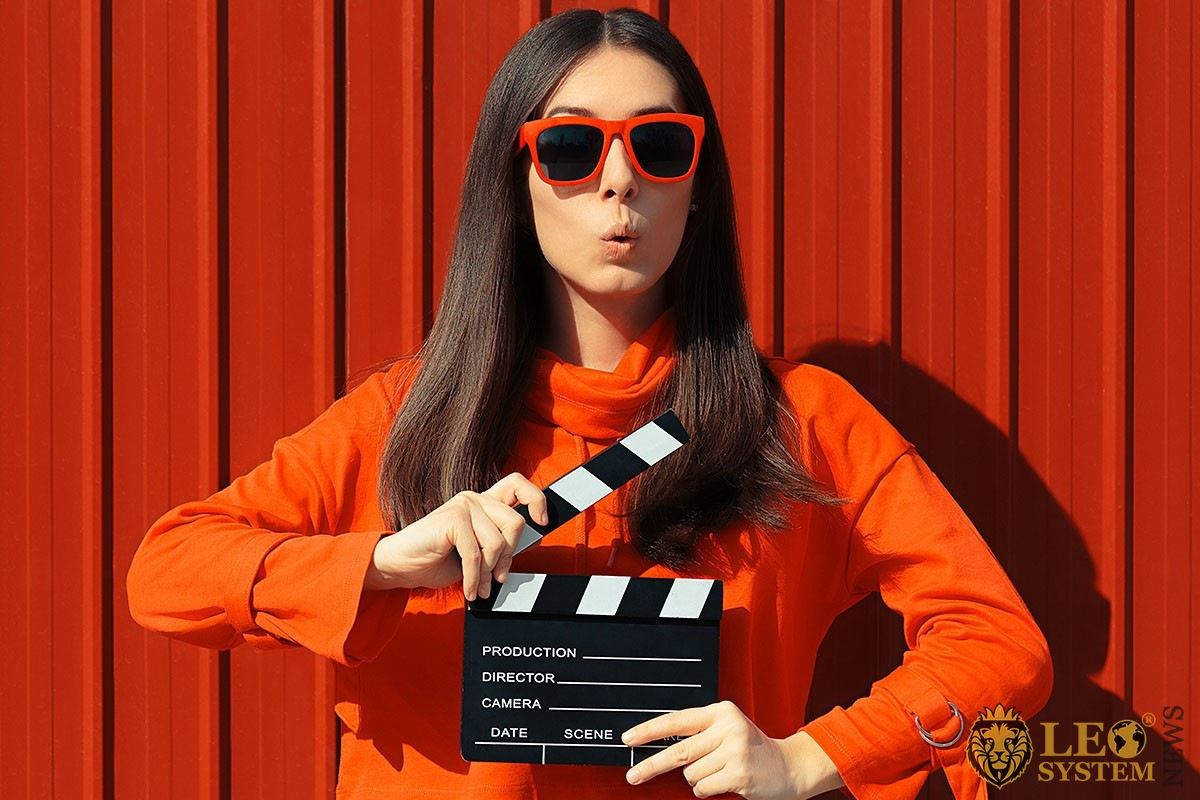 Image of disciplined woman with clapperboard in hands