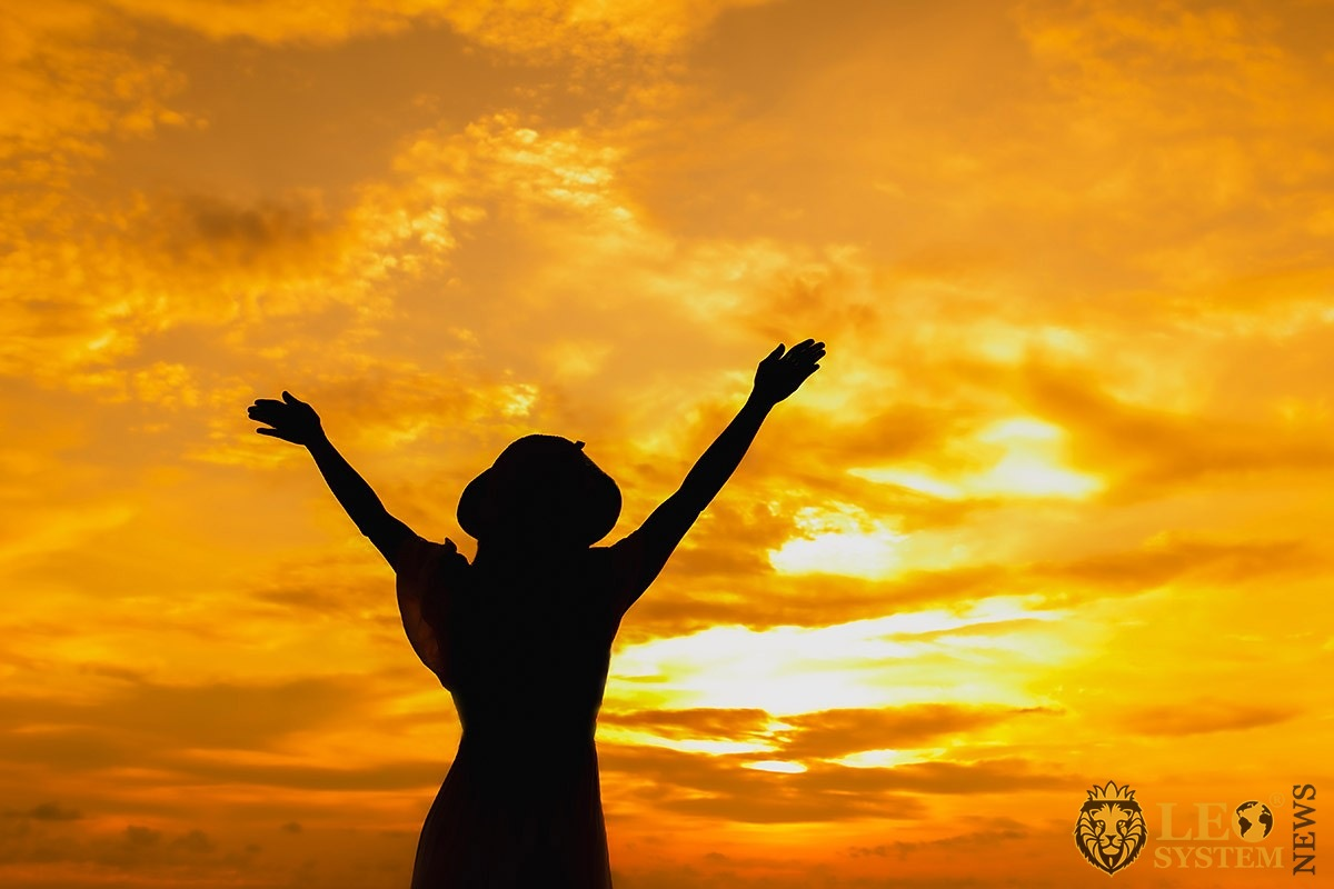 Woman spreads her hands freely at sunset