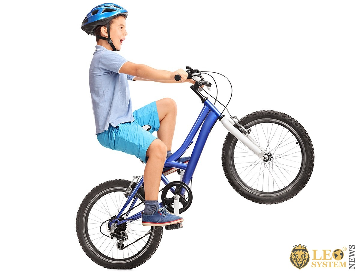 Self-confident child rides the back wheel of his bike