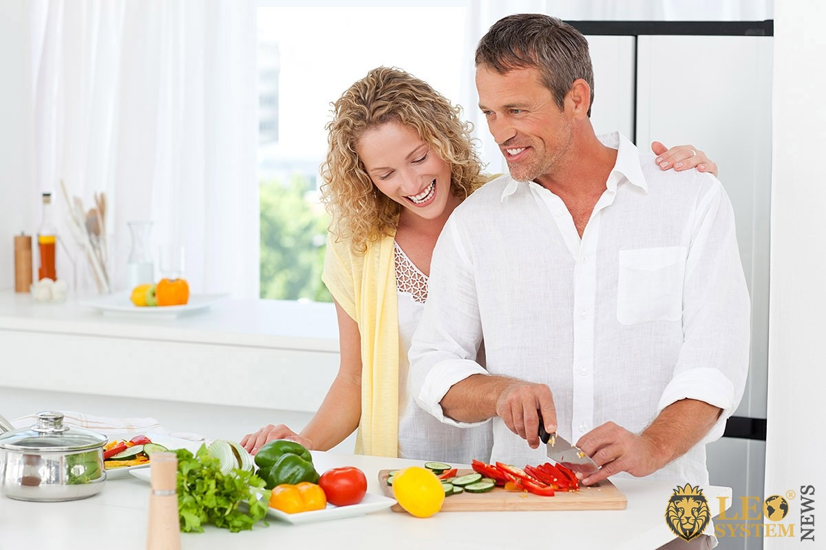 Man preparing food in the kitchen with his wife