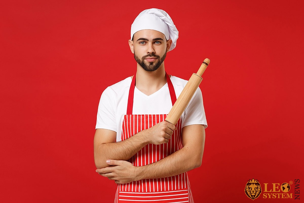 Cute man in a cap and with a rolling pin in his hands