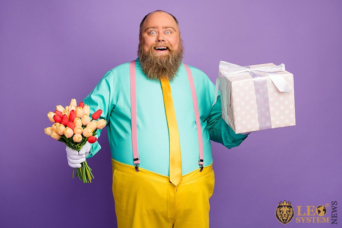 Image of a cheerful man with flowers and a gift