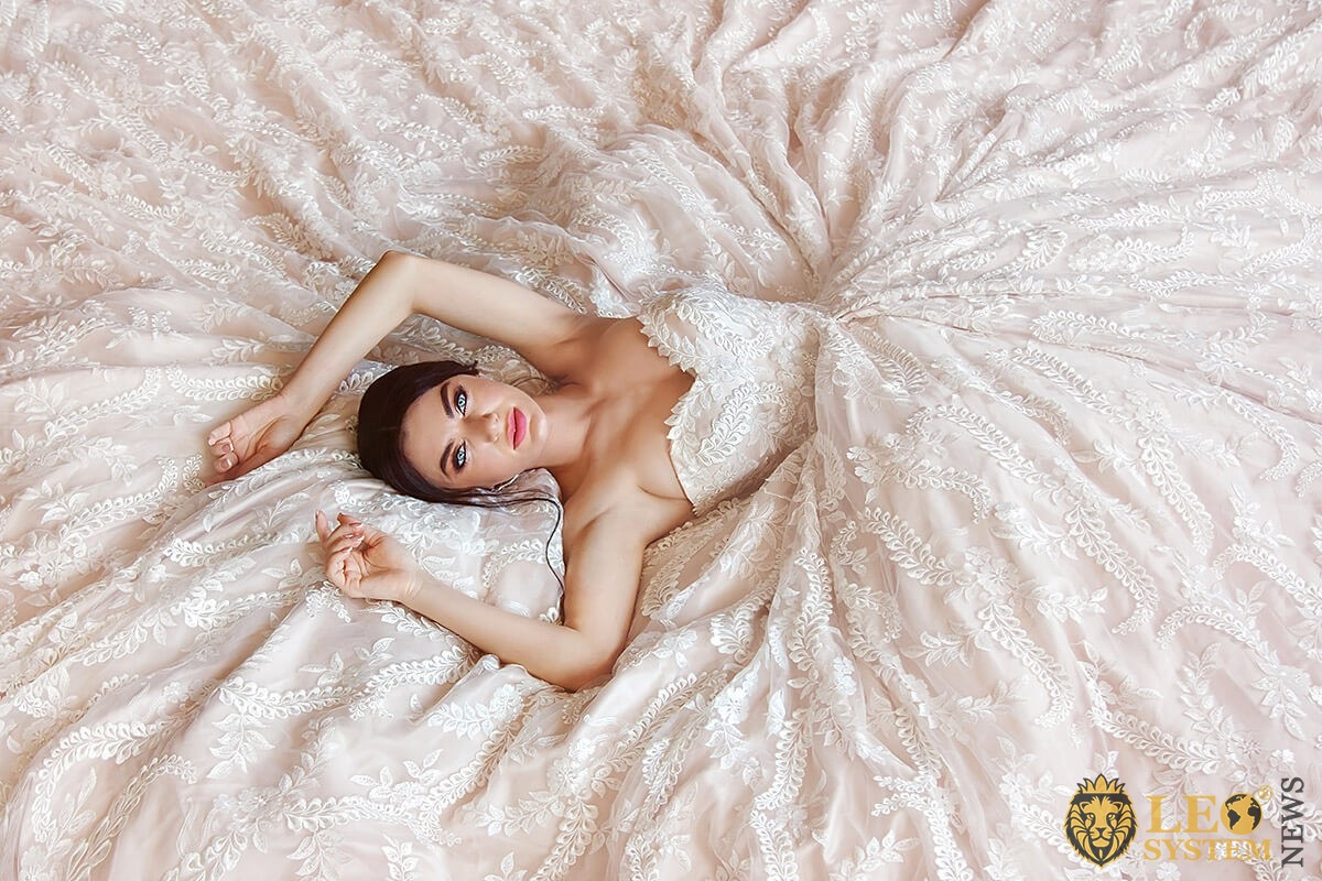 Beautiful bride lies in a very magnificent dress