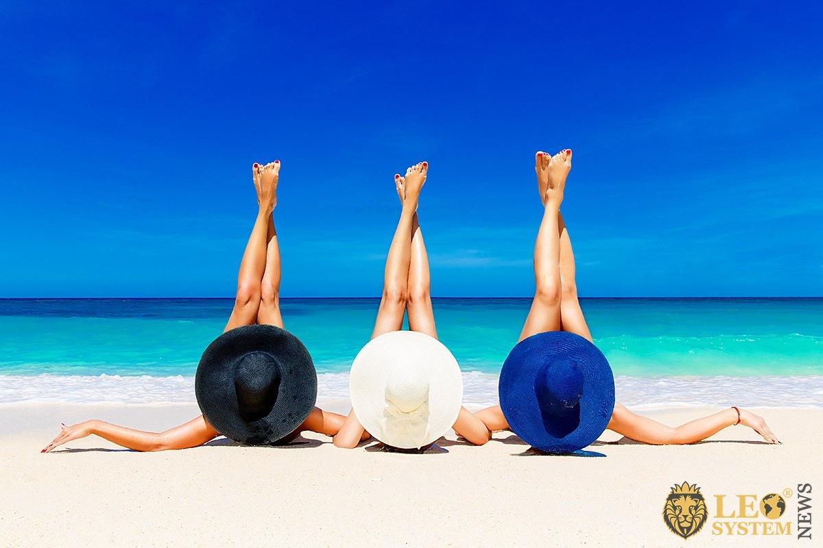 Image of three sunbathing woman on the beach