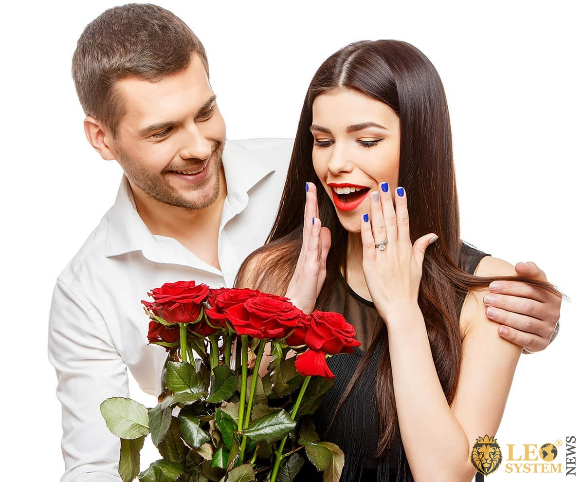 Husband gives a bouquet of red roses to his wife
