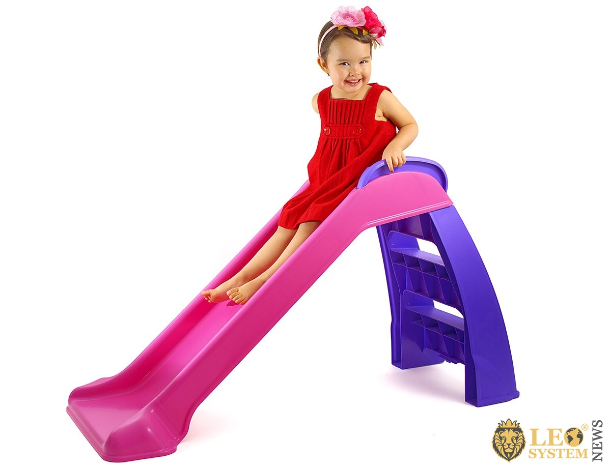 A little girl riding down a children's slide