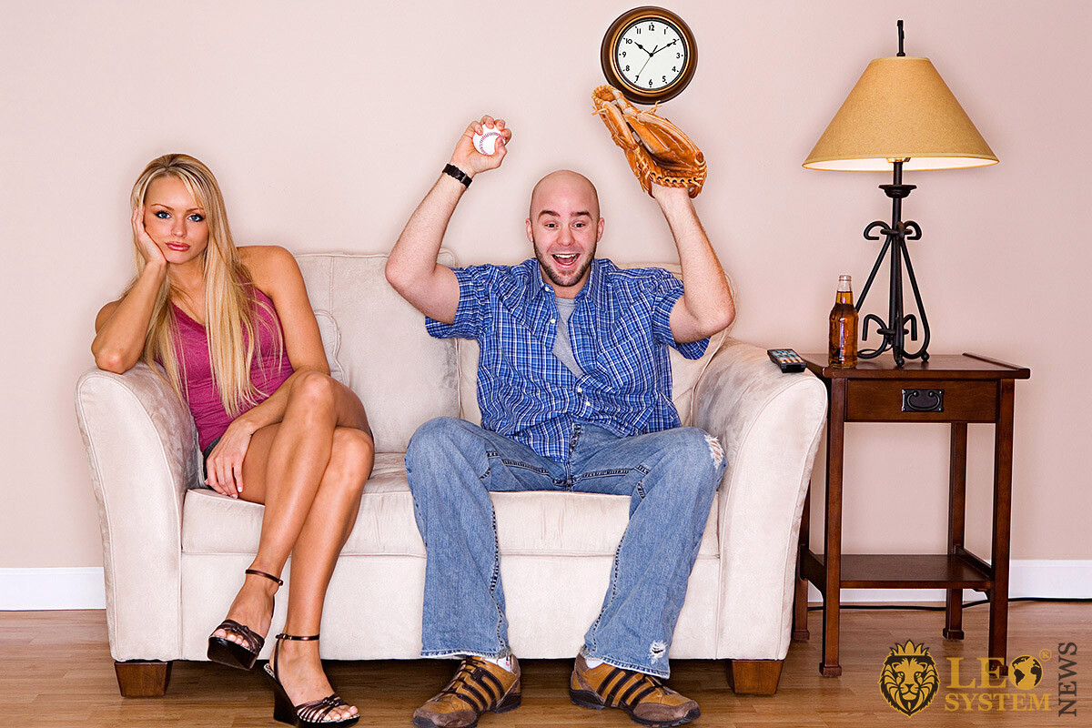 Adult man with baseball glove and ball watching TV