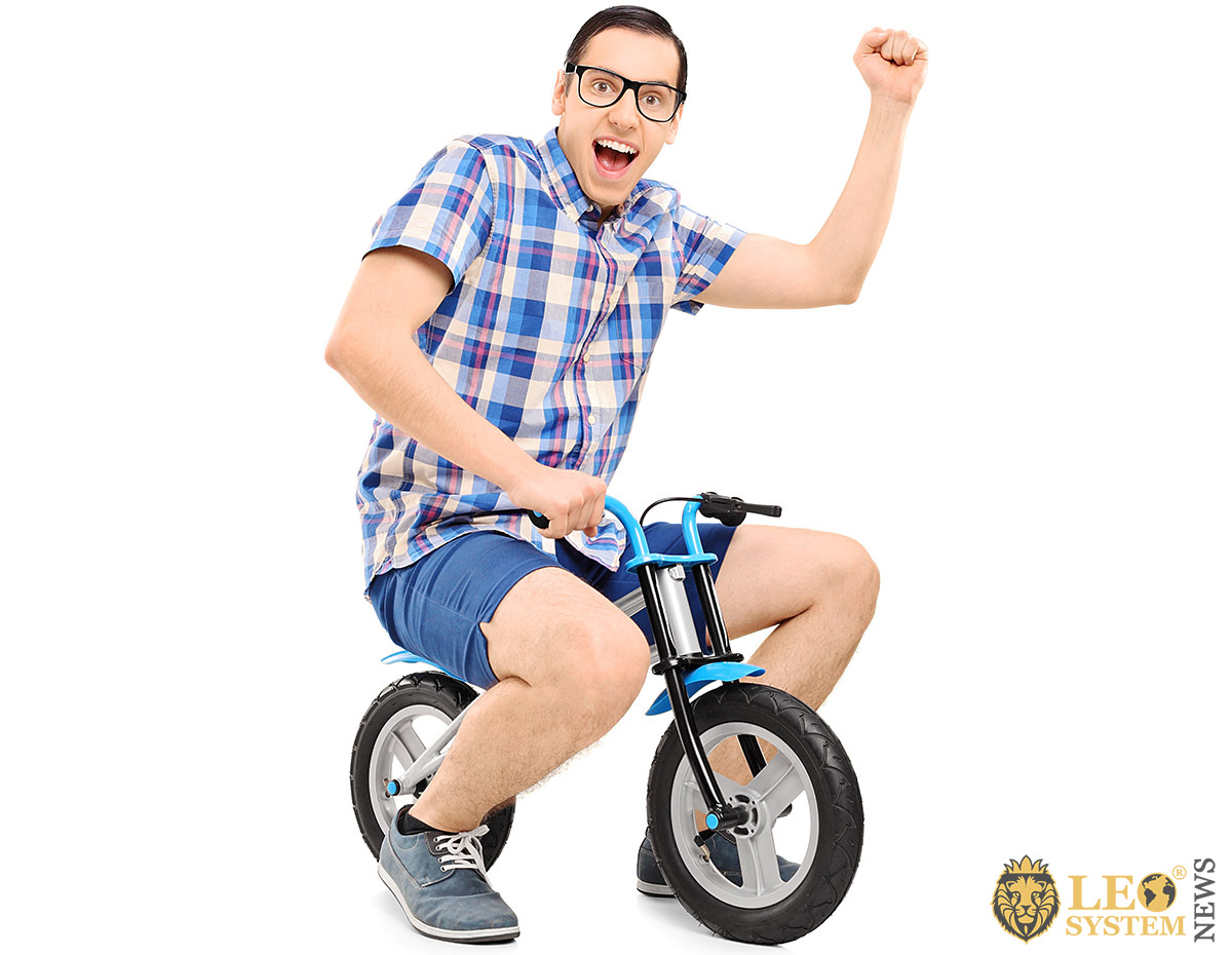 Cheerful adult man rides a child's little bike