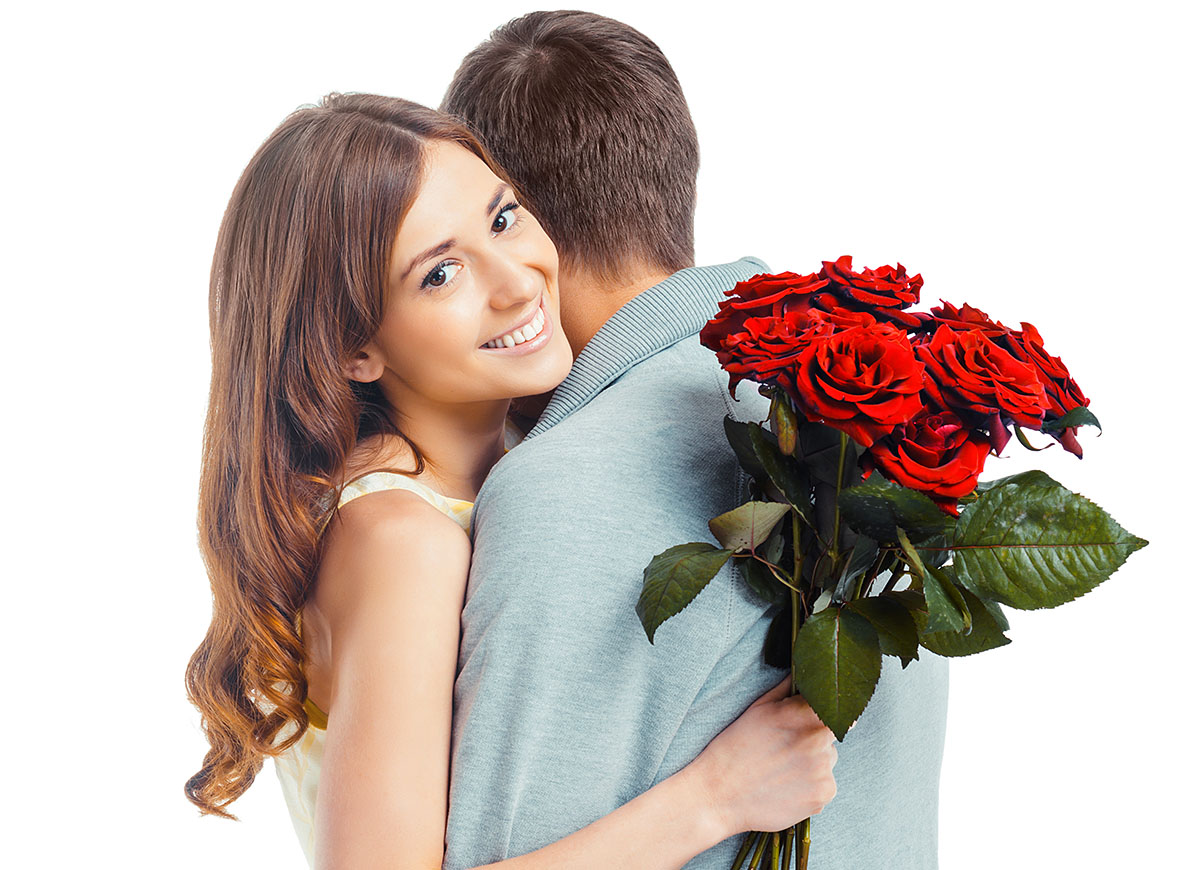Young man hugging his girlfriend and gives her a bouquet of flowers