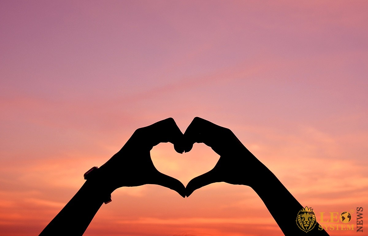 Image of hands in the form of a heart of love at sunset