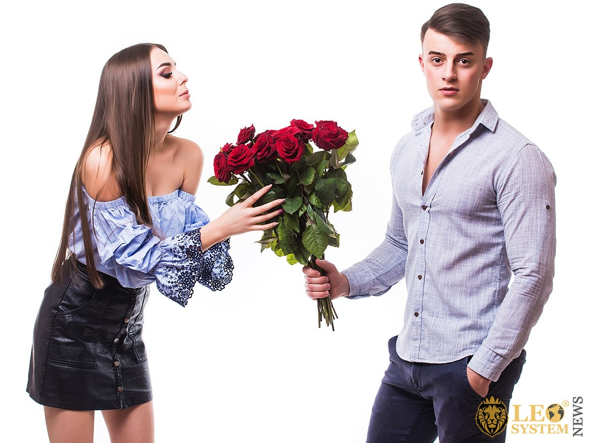 Young man gives flowers to his girlfriend