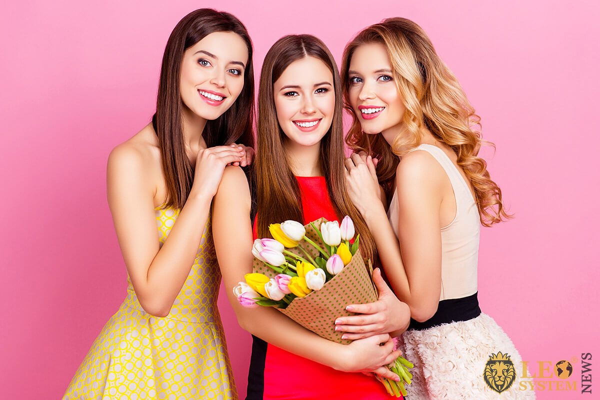 Three attractive women with a bouquet of flowers