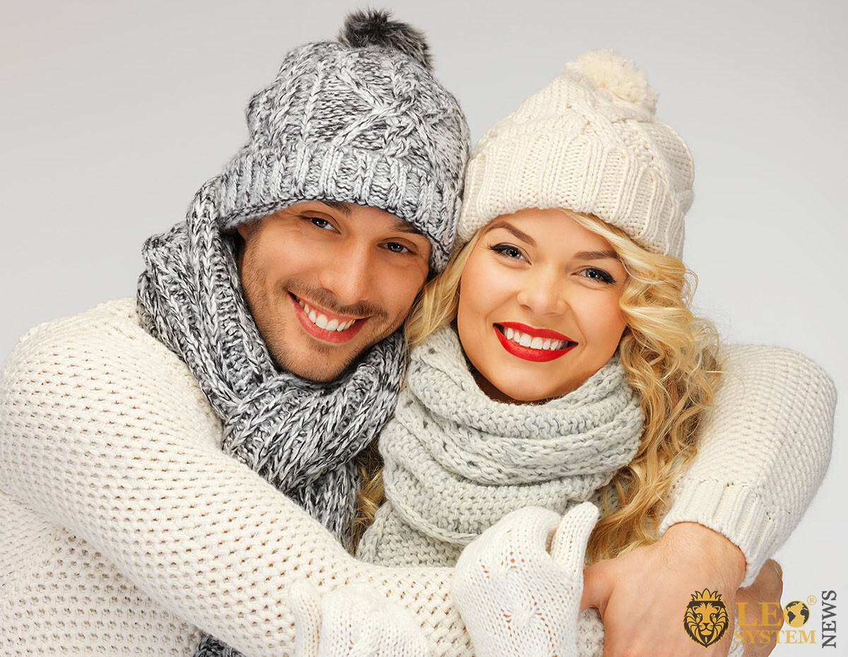 Cute man and woman in warm clothes and hats