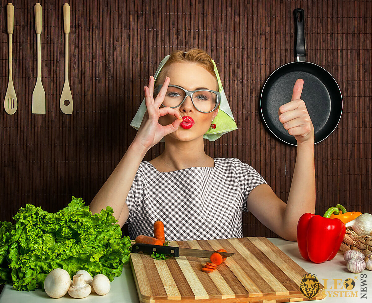 Woman with kitchen utensils shows various hand gestures