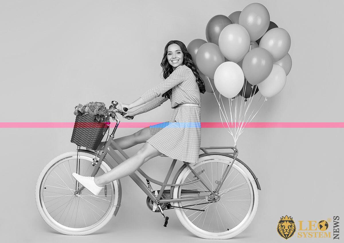 Joyful woman on bike and with balloons