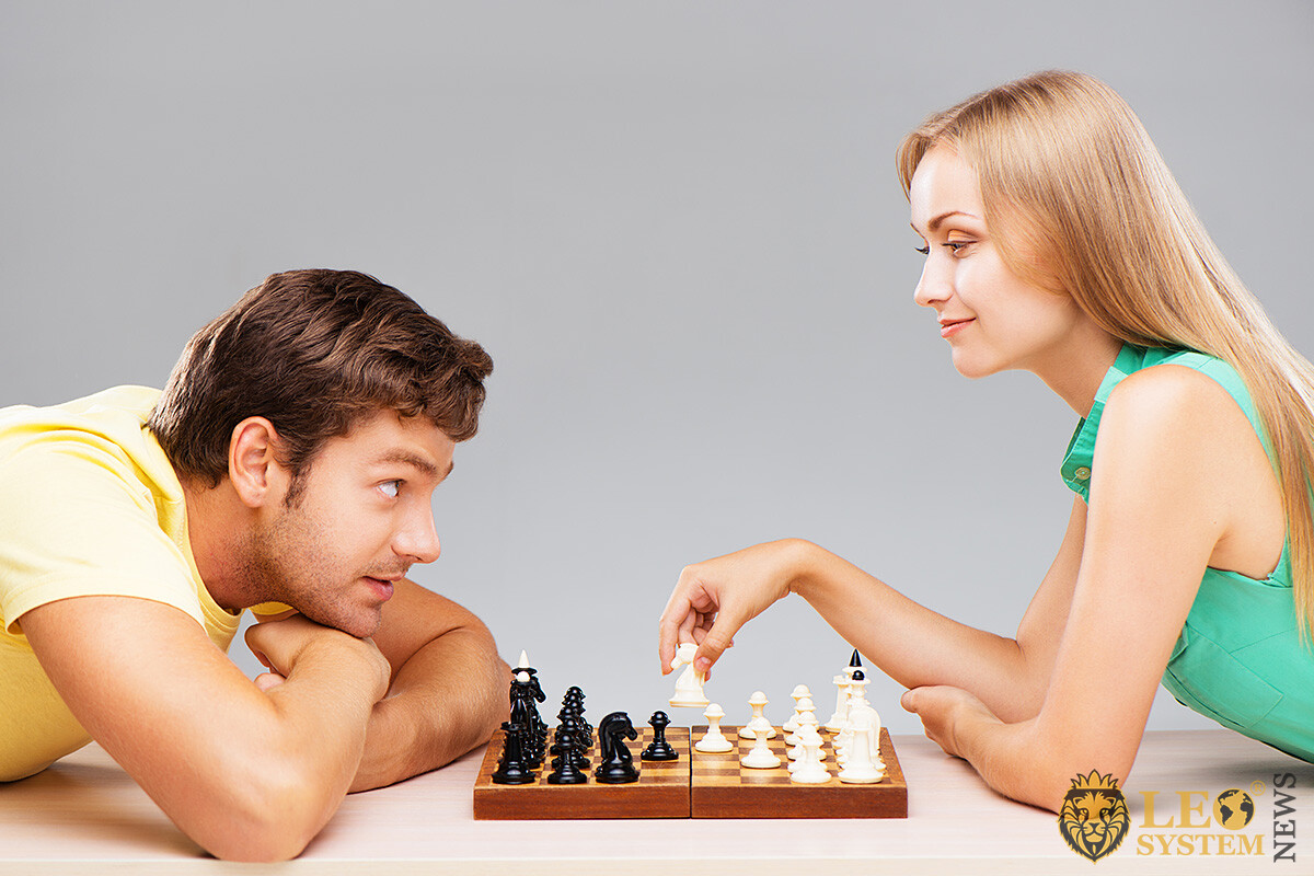 Friendly couple of man and woman playing chess