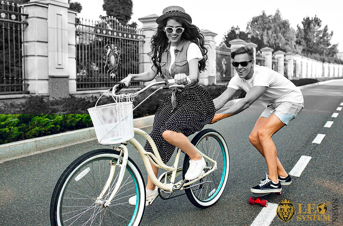 Image of a girl on a bicycle and a guy on a skateboard