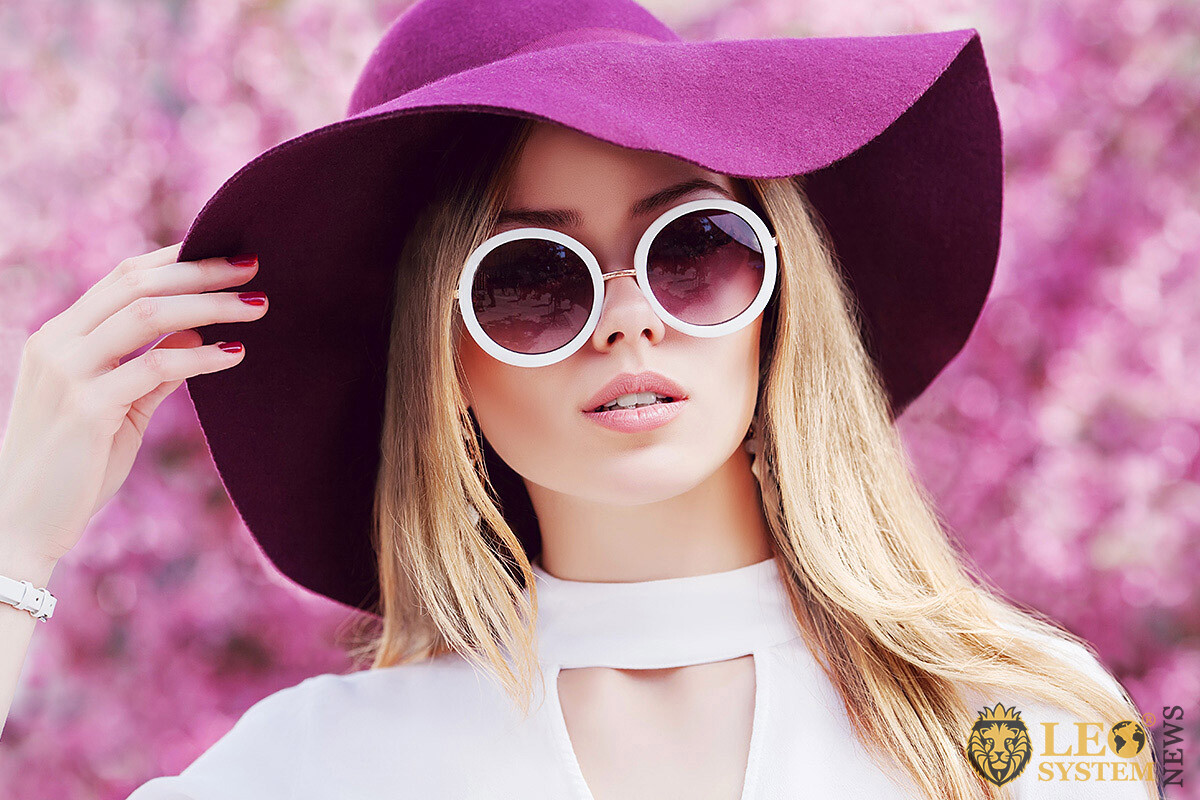 Image of elegant woman in purple hat and sunglasses