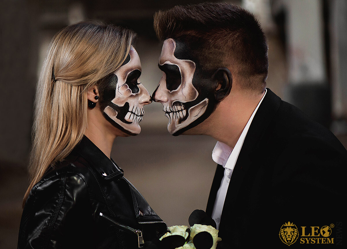 Man and woman with painted masquerade faces look at each other