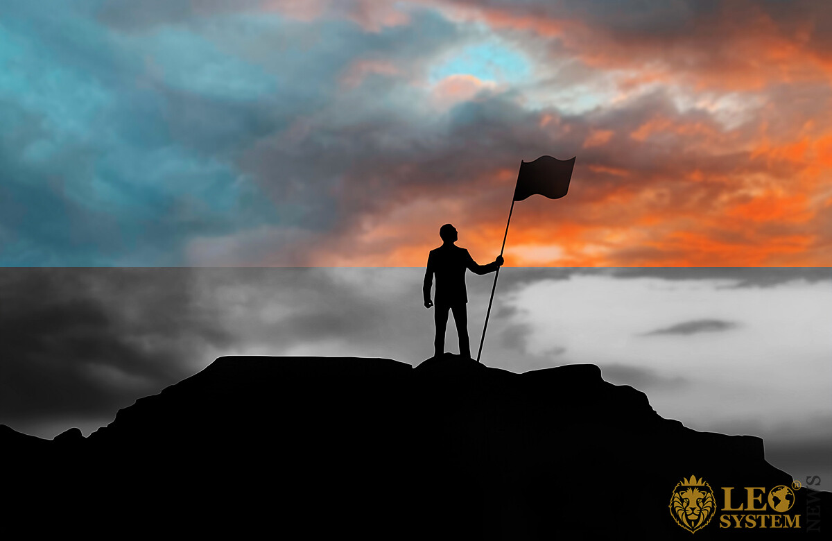 Image of a man on top of a mountain with a flag