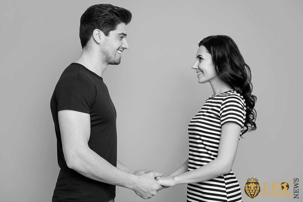 A man holds his woman's hands and looks into her eyes