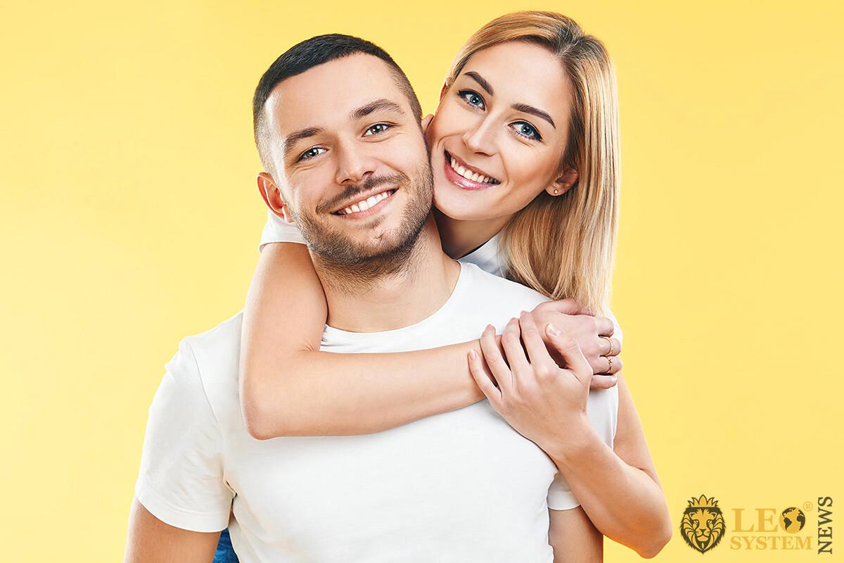 A girl in love gently hugs her boyfriend