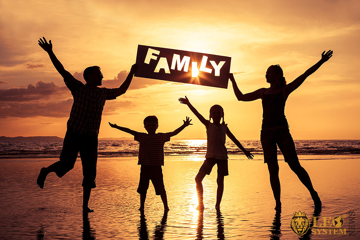 Happy and cheerful family by the sea at sunset
