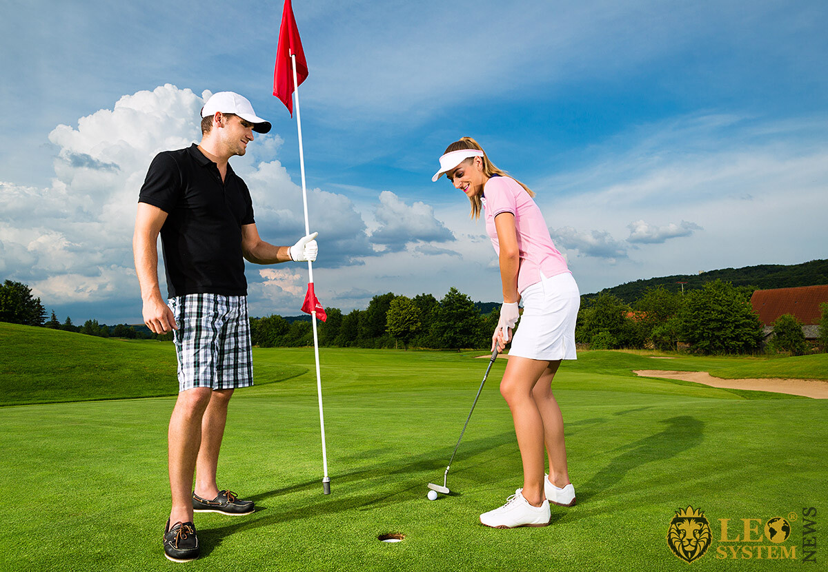 Cute couple on a date playing golf