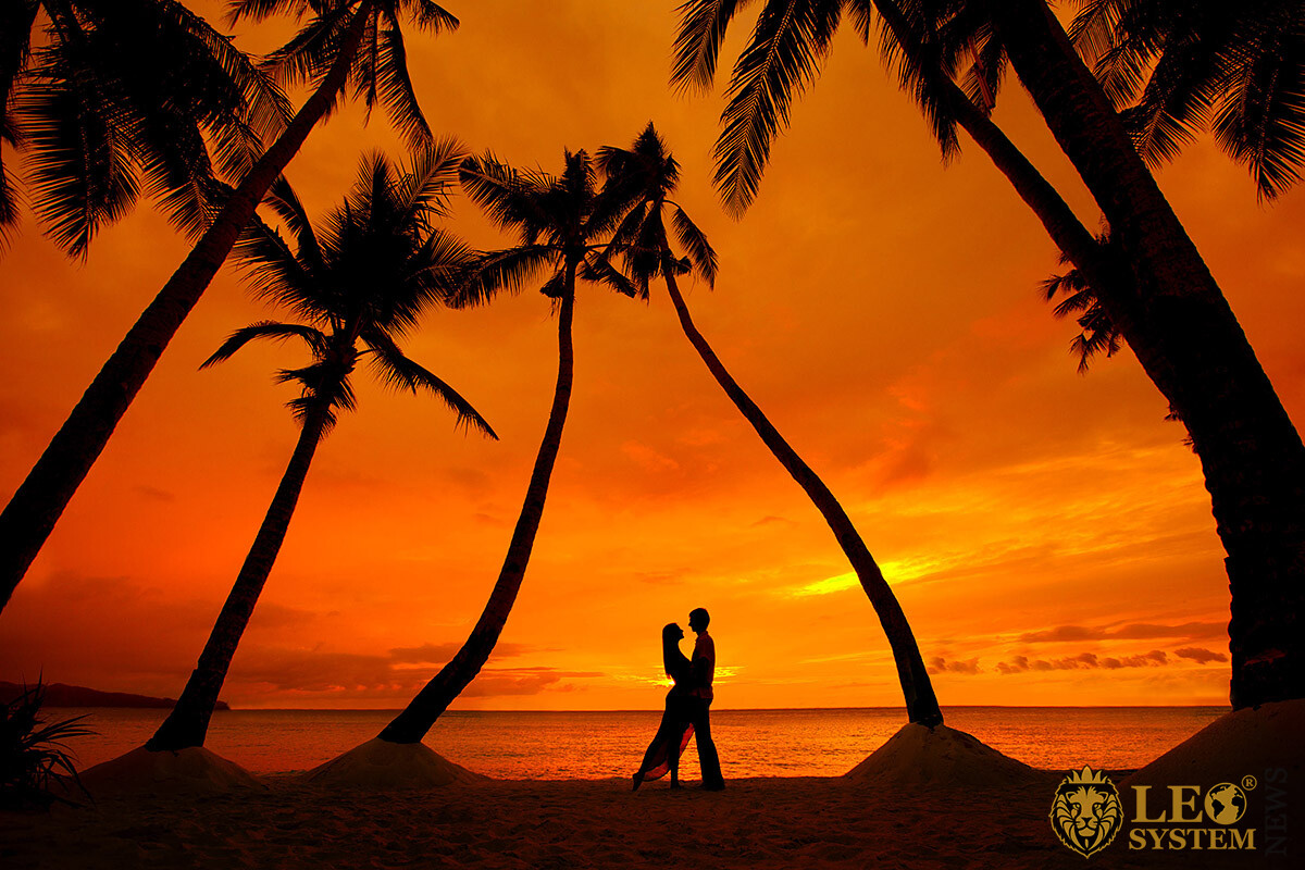 Image of a romantic couple on a tropical beach with palm trees at sunset time