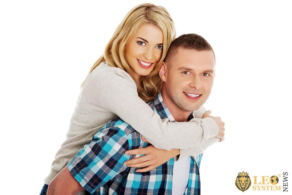 Young girl hugs her boyfriend tenderly
