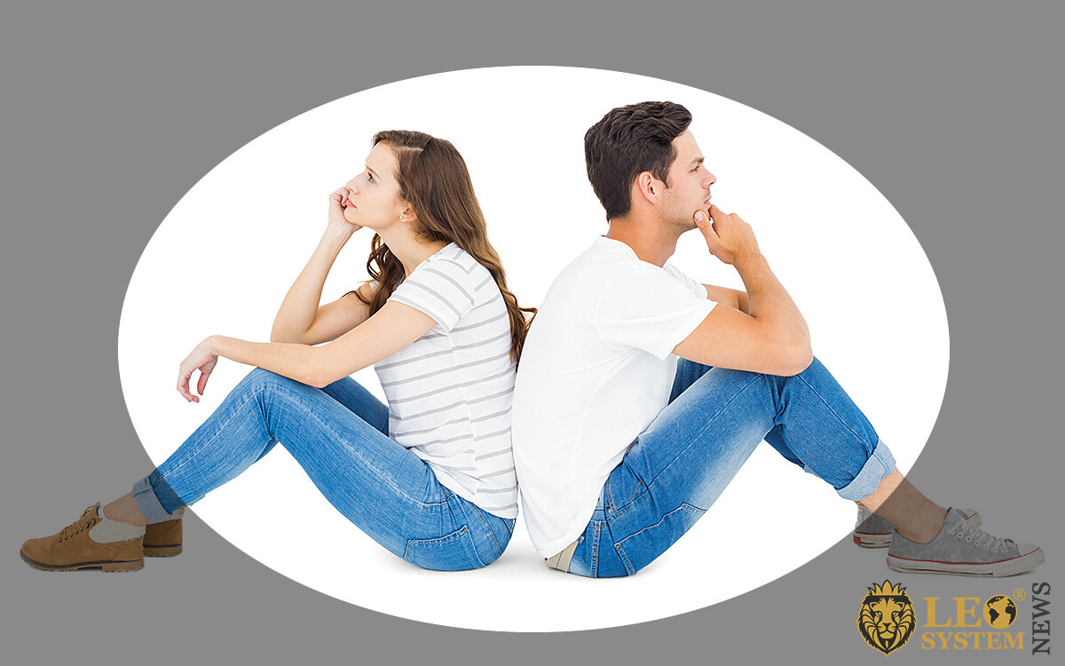Image of an indifferent man sitting with his back to his wife