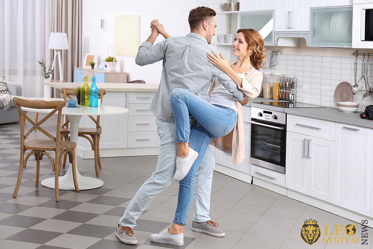 Image of happy dancing couple in the kitchen