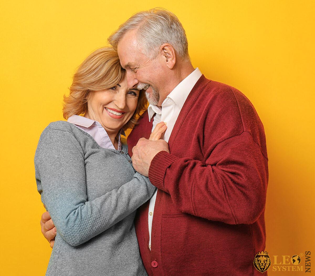 Happy elderly man hugs his woman tenderly
